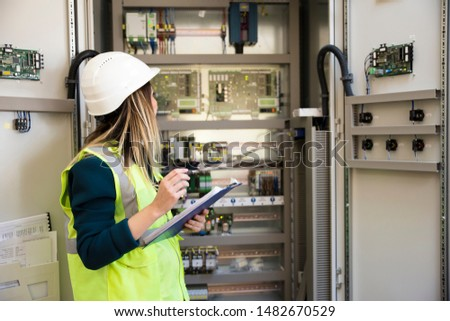 Young businesswoman standing in front of the control panel in the control room #1482670529