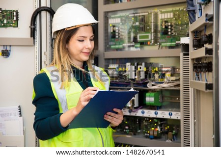 Young businesswoman standing in front of the control panel in the control room #1482670541