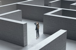 Young businesswoman standing in middle of a gray concrete labyrinth. Business and challenge concept.