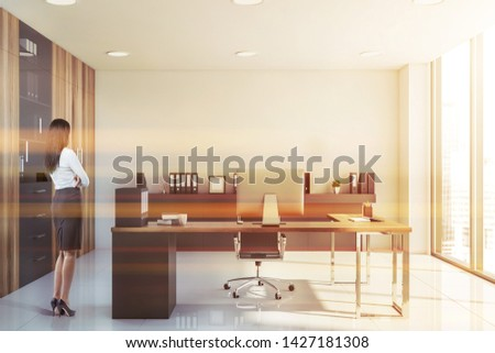 Young businesswoman standing in modern CEO office with white walls and floor, wooden computer desk, shelves with folders and bookcases. Toned image #1427181308