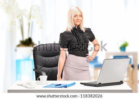 Young businesswoman standing next to desk with laptop at her workplace