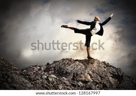 young businesswoman standing on one leg atop of mountain against diagram background