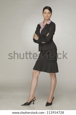 Young businesswoman standing with arms crossed