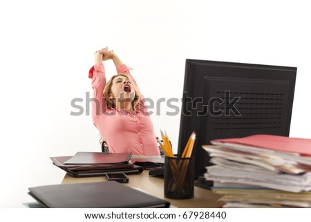 Young businesswoman stretching at desk