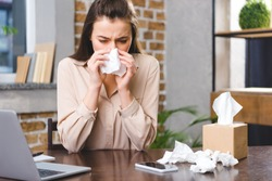 young businesswoman suffering from allergy at workplace