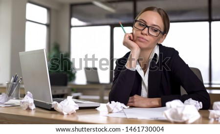 Young businesswoman suffering startup ideas lack, looking at crumpled papers