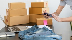 Young businesswoman taking pictures of clothes for sale online with laptops and boxes on the table