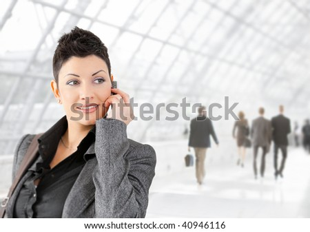 Young businesswoman talking on mobile phone on office lounge, smiling.