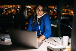 Young businesswoman talking on the phone and using a laptop at her office desk late into the night in front of windows overlooking the city