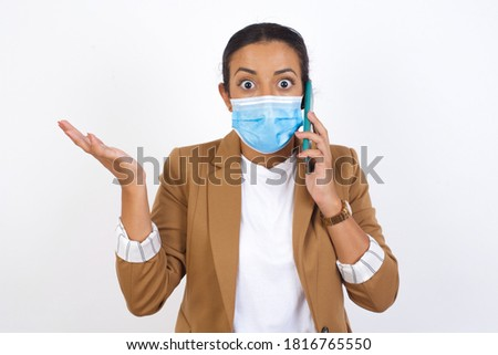 Young businesswoman talking on the phone over isolated background stressed with hand on face, shocked with shame and surprise face, angry and frustrated. Fear and upset for mistake.