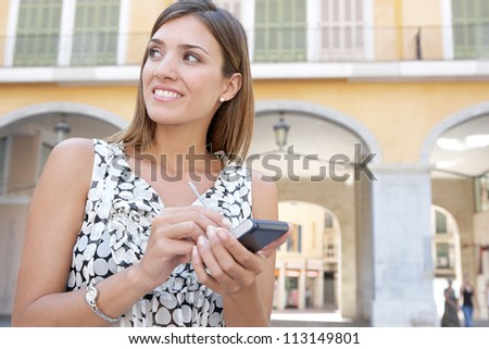 Young businesswoman using a digital tablet while standing next to classic arches.