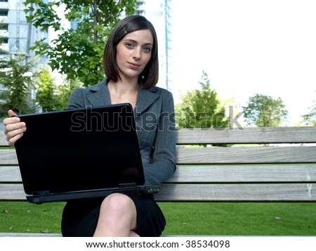 Young businesswoman using a laptop computer sitting on a bench