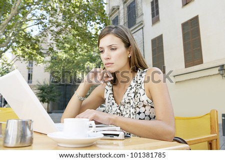 Young businesswoman using a laptop computer while sitting in a coffee shop in the city, outdoors.