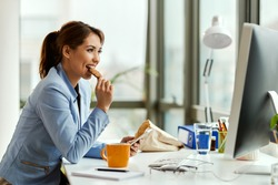 Young businesswoman using cell phone while eating a cookie at her office desk.