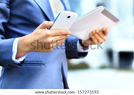 young businesswoman using digital tablet and mobile phone over building background