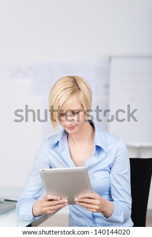 Young businesswoman using digital tablet while sitting on chair in office