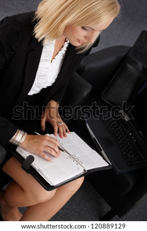 Young businesswoman using personal organizer, taking notes, elevated view.