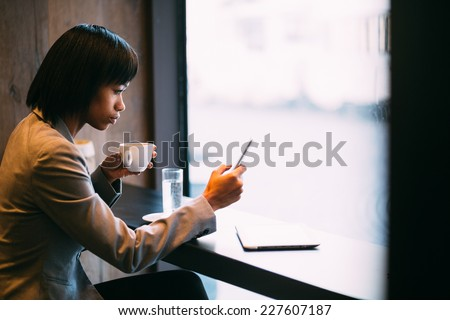 Young businesswoman using phone in coffee shop stock photo