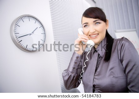 Young businesswoman wearing brown shirt, talking on landline phone in office, smiling.
