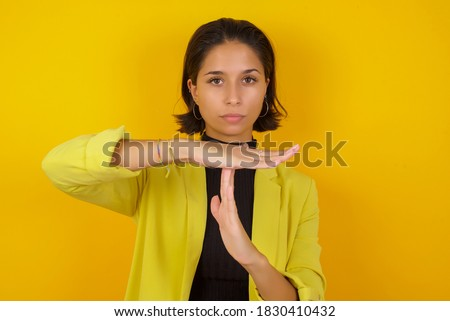 Young businesswoman wearing casual turtleneck sweater and jacket being upset showing a timeout gesture, needs stop, asks time for rest after hard work, demonstrates break hand sign Stock photo ©