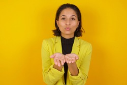 Young businesswoman wearing casual turtleneck sweater and jacket sending blow kiss with pout lips and holding palms to send air kiss.