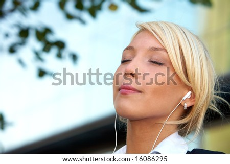 Young businesswoman wearing earphones in city, eyes closed