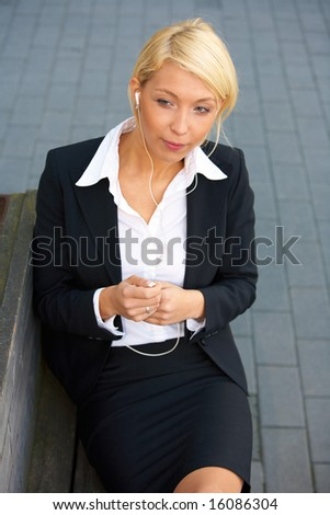 Young businesswoman wearing earphones, sitting on street bench