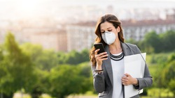 Young businesswoman wearing face mask outside during Covid-19 coronavirus health crisis. Professional woman using her smartphone.
