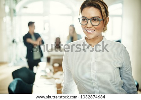 Young businesswoman wearing glasses and smiling while standing in an office with colleagues working behind her #1032874684