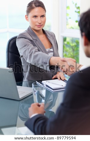 Young businesswoman welcomes customer in her office