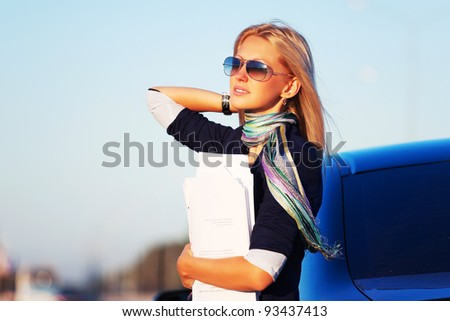 Young businesswoman with a car