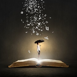 Young businesswoman with black umbrella standing on book