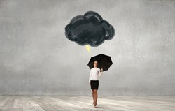 Young businesswoman with black umbrella standing under black cloud