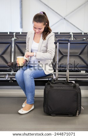 Young businesswoman with coffee cup checking time while waiting for flight at airport lobby