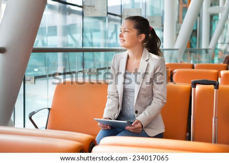 Young businesswoman with digital tablet waiting for flight at airport lobby