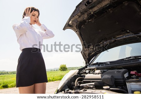 Young businesswoman with hands on head standing by broken down car at countryside.