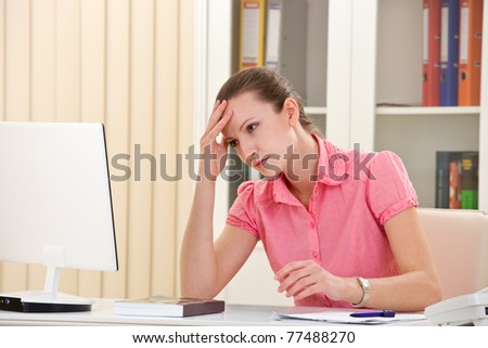 young businesswoman with headache sitting on her desk