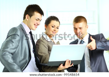 Young businesswoman with her colleagues using laptop