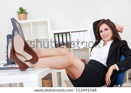 Young Businesswoman With Her Legs On The Desk.
