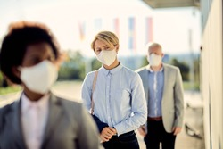Young businesswoman with kn95 face mask waiting in line on a safe distance during COVID-19 epidemic.