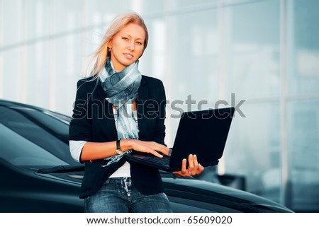 Young businesswoman with laptop against office windows.