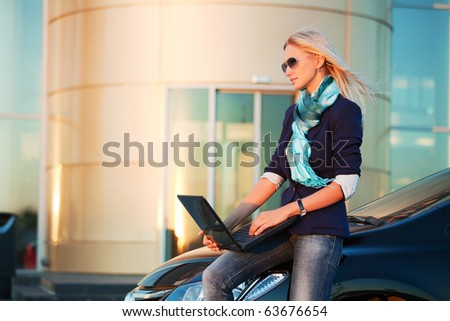 Young businesswoman with laptop by the sunset light.