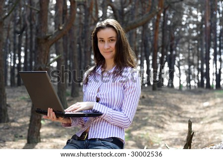 young businesswoman with laptop working outdoors