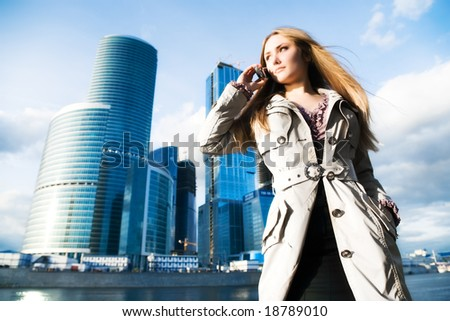 Young businesswoman with mobile phone. On modern city background.