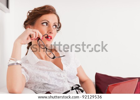 Young businesswoman with notebook sits on the sofa.