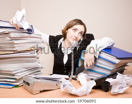 Young businesswoman with tons of documents calling phone