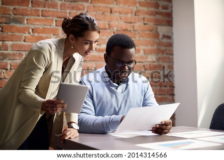 Young businesswoman with touchpad and her African American colleague going through reports while working in the office.  Stock fotó ©