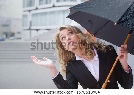 Young businesswoman with umbrella checking to see if it's still raining