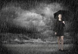 Young businesswoman with umbrella standing in rain