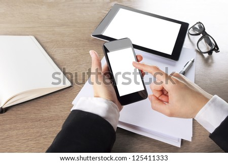 Young businesswoman working with digital tablet computer and smart phone. hands touching on digital mobile phone in a office